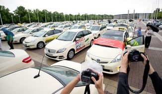 FILE - In this June 11, 2014 file photo taxi drivers gather after a protest drive against the competition from Internet and mobile applications designed for calling cabs in Berlin, Germany. Berlin taxi drivers are now celebrating a decision by authorities to ban the ridesharing service Uber from operating in the city. The Berlin Taxi Drivers' Association said Thursday, Aug. 14, 2014, that the move means its members aren't put at a disadvantage by having to abide by rules that Uber doesn't. (AP Photo/dpa, Joerg Carstensen, File)