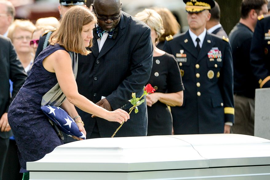 Dr. Susan Myers, the wife of Army Maj. Gen. Harold J. Greene puts a rose on his coffin during his funeral service at Section 60 at Arlington National Cemetery, Arlington, Va., Thursday, August 14, 2014. Greene was killed in Afghanistan while at the national military academy in Kabul. He was the highest-ranking U.S. Army officer killed in combat since the Vietnam War. (Andrew Harnik/The Washington Times)