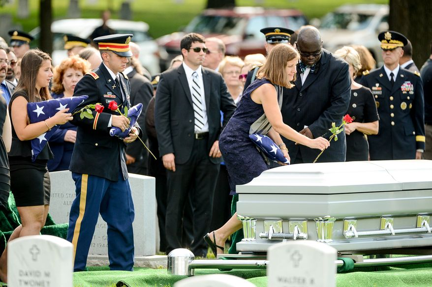 The children of Army Maj. Gen. Harold J. Greene, his daughter Amelia Greene, left, and his son Army 1st Lt. Matthew Greene, second from left, watches as Dr. Susan Myers, the wife of Army Maj. Gen. Harold J. Greene puts a rose on his coffin during his funeral service at Section 60 at Arlington National Cemetery, Arlington, Va., Thursday, August 14, 2014. Greene was killed in Afghanistan while at the national military academy in Kabul. He was the highest-ranking U.S. Army officer killed in combat since the Vietnam War. (Andrew Harnik/The Washington Times)