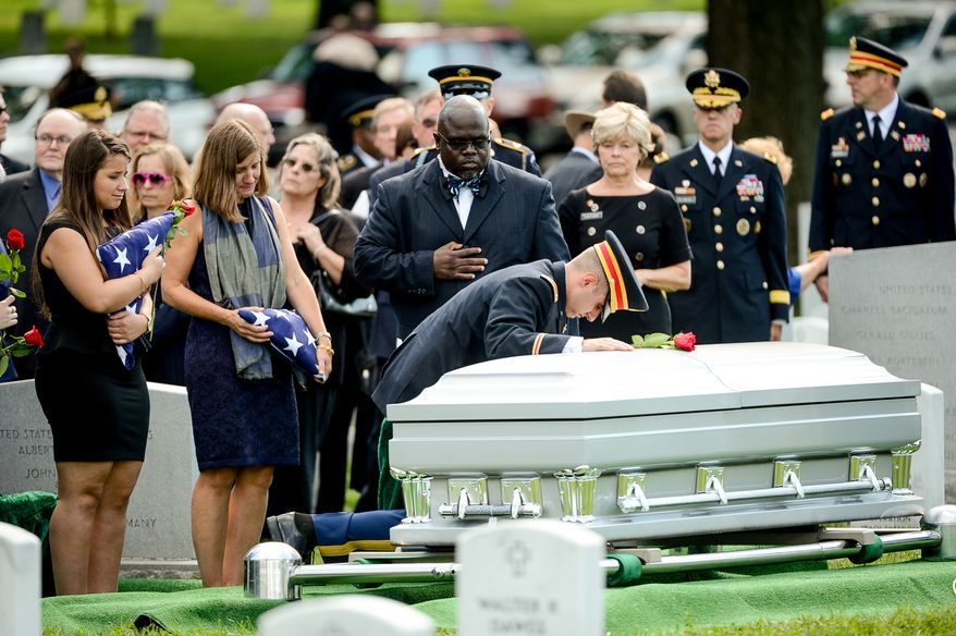 The family of Army Maj. Gen. Harold J. Greene, from left, daughter Amelia Greene, wife Dr. Susan Myers, and son Army 1st Lt. Matthew Greene, each take turns placing a rose on his coffin during his funeral service at Section 60 at Arlington National Cemetery, Arlington, Va., Thursday, August 14, 2014. Greene was killed in Afghanistan while at the national military academy in Kabul. He was the highest-ranking U.S. Army officer killed in combat since the Vietnam War. (Andrew Harnik/The Washington Times)