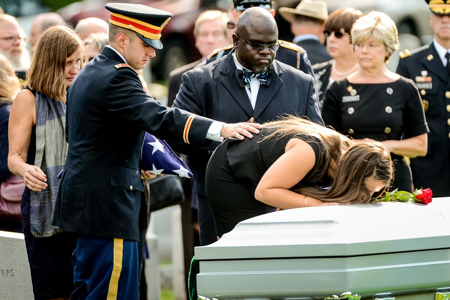 The family of Army Maj. Gen. Harold J. Greene, from left, wife Dr. Susan Myers, son Army 1st Lt. Matthew Greene, and daughter Amelia Greene, each take turns placing a rose on his coffin during his funeral service at Section 60 at Arlington National Cemetery, Arlington, Va., Thursday, August 14, 2014. Greene was killed in Afghanistan while at the national military academy in Kabul. He was the highest-ranking U.S. Army officer killed in combat since the Vietnam War. (Andrew Harnik/The Washington Times)