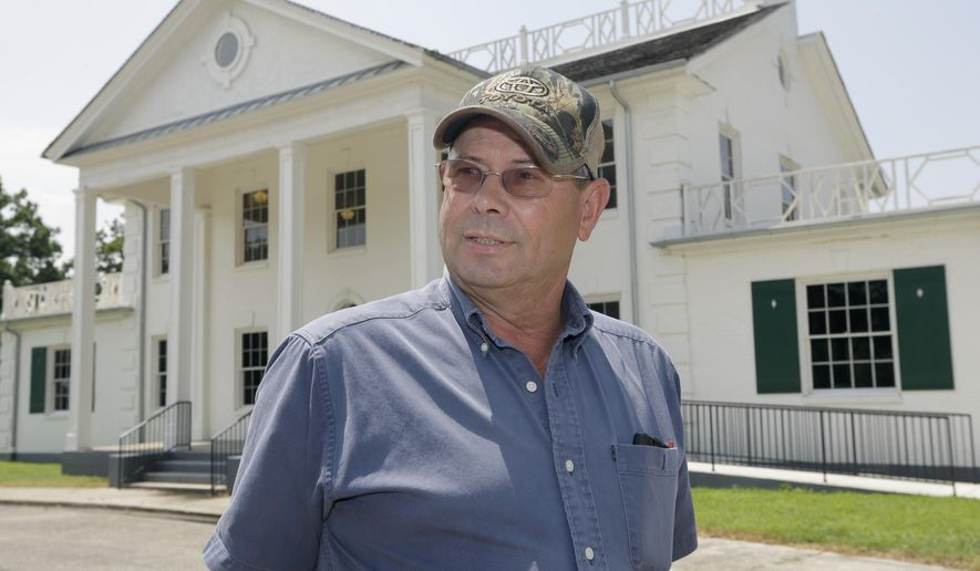 In this photo taken Friday, Aug. 8, 2014, in Dyess, Ark., Dyess Mayor Larry Sims is interviewed in front of the restored Depression era Administration Building of the Resettlement Administration's Dyess Colony. Singer Johnny Cash spent his childhood at a home in the colony. (AP Photo/Danny Johnston)
