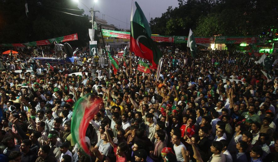Supporters of Pakistan's cricketer-turned-politician Imran Khan gather to march to Islamabad from Lahore, Pakistan, Thursday, Aug. 14, 2014. Thousands of opposition protesters on Thursday joined large convoys headed to Pakistan's capital Islamabad for a mass rally to demand the ouster of the prime minister over allegations of vote fraud. (AP Photo/K.M. Chaudary)