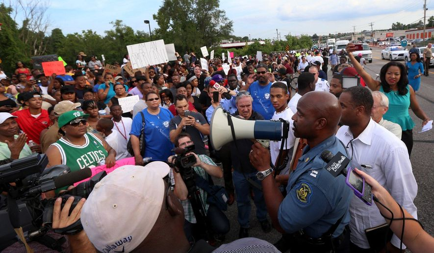 Missouri State Highway Patrol Capt. Ronald Johnson addresses the crowd of protesters, asking them to stay on the sidewalk and not block traffic Thursday, Aug. 14, 2014, in Ferguson, Mo. The Missouri Highway Patrol took control of a St. Louis suburb Thursday, stripping local police of their law-enforcement authority after four days of clashes between officers in riot gear and furious crowds protesting the death of an unarmed black teen shot by an officer. (AP Photo/St. Louis Post-Dispatch, David Carson)