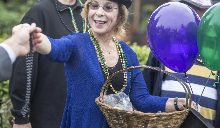 Debra Waterman passes out New Orleans party beads before the processional starts, Thursday, Aug. 14, 2014, in Langley, Wash. The New Orleans style procession, led by the South Whidbey High School Jazz Ensemble, marched through downtown Langley Thursday in memory of former Seattle mayor Paul Schell. (AP Photo/The Seattle Times, Steve Ringman)