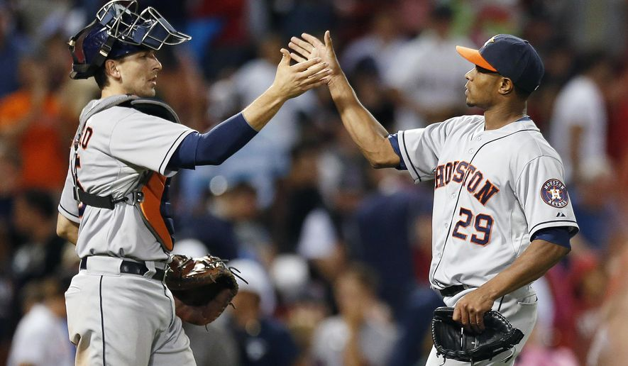 Houston Astros' Tony Sipp (29) and Jason Castro celebrate after defeating the Boston Red Sox 5-3 in the 10th inning of a baseball game in Boston, Friday, Aug. 15, 2014. (AP Photo/Michael Dwyer)