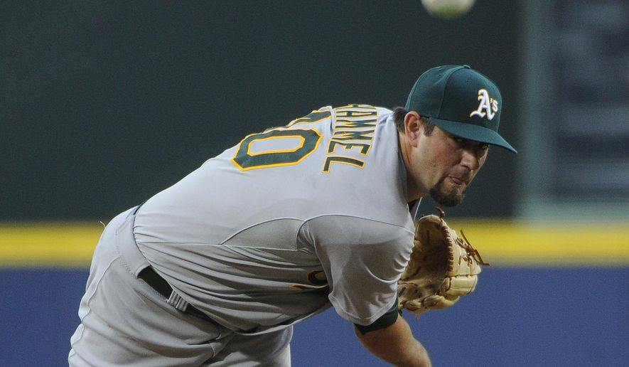 Oakland Athletics starting pitcher Jason Hammel delivers to the Atlanta Braves during the first inning of a baseball game against the Oakland Athletics Friday, Aug. 15, 2014, in Atlanta. (AP Photo/David Tulis)