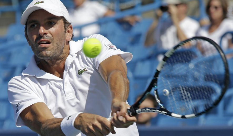 Julien Benneteau, from France, hits a backhand against Stan Wawrinka, from Switzerland, during a match at the Western & Southern Open tennis tournament, Friday, Aug. 15, 2014, in Mason, Ohio. (AP Photo/Al Behrman)