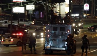 Police attempt to secure a street after a clash with protesters Wednesday, Aug. 13, 2014, in Ferguson, Mo.  Protests in the St. Louis suburb rocked by racial unrest since a white police officer shot an unarmed black teenager to death turned violent Wednesday night, with people lobbing molotov cocktails at police who responded with smoke bombs and tear gas to disperse the crowd.  (AP Photo/Jeff Roberson)