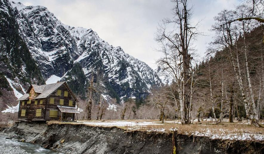 FILE - This April 2014 file photo provided by the Olympic National Park service shows a log cabin teetering on the eroding bank of the Quinault River in Olympic National Park in Washington. The park has awarded a $124,000 contract to the Monroe House Moving company of Carlsborg to move the Enchanted Valley Chalet to safer ground.   (AP Photo/Olympic National Park Service, File)