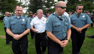 Ferguson Police Chief Tom Jackson is surrounded by his officers as he leaves a news conference in Forestwood Park on Friday, Aug. 15, 2014.  Jackson took questions in the quiet park after earlier identifying Darren Wilson as the officer who shot Michael Brown. (AP Photo/St. Louis Post-Dispatch, Robert Cohen)