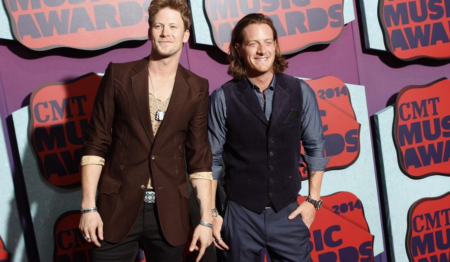 """FILE - This June 4, 2014 file photo shows Brian Kelley, left, and Tyler Hubbard of the musical group Florida Georgia Line arrive at the CMT Music Awards at Bridgestone Arena on in Nashville, Tenn. The duo will release their latest album, """"Anything Goes,"""" out Oct. 14. (Photo by Wade Payne/Invision/AP, File)"""