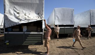 Drivers prepare to show the cargo to journalists in a field where the aid convoy is parked in Kamensk-Shakhtinsky, Russia, Friday, Aug. 15, 2014. (AP Photo/Pavel Golovkin)