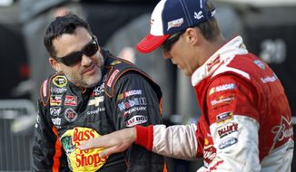 FILE - In this May 22, 2014, file photo, Tony Stewart, left, talks with Kevin Harvick before qualifying for a NASCAR Sprint Cup series auto race at Charlotte Motor Speedway in Concord, N.C.  (AP Photo/Terry Renna, File)