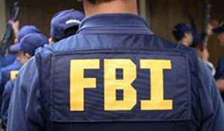 An FBI agent waits to receive his assigned weapon. (Image: FBI.gov) **FILE **