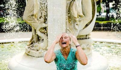 Este Strydom of Bloemfontein, South Africa cools off in the fountain at Dupont Circle, Washington, D.C., Tuesday, June 17, 2014. (Andrew Harnik/The Washington Times)