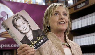 "In this Aug. 13, 2014, photo, former Secretary of State Hillary Rodham Clinton holds her memoir ""Hard Choices"" at Bunch of Grapes Bookstore, in Vineyard Haven, Mass., on the island of Martha's Vineyard, during a book signing event for her memoir ""Hard Choices.""  Clinton's split with President Barack Obama over a foreign policy ""organizing principle"" isn't likely to be the last time differences emerge between the two. How she handles those breaks could be among her biggest challenges to a successful run for president in 2016. (AP Photo/Steven Senne)"