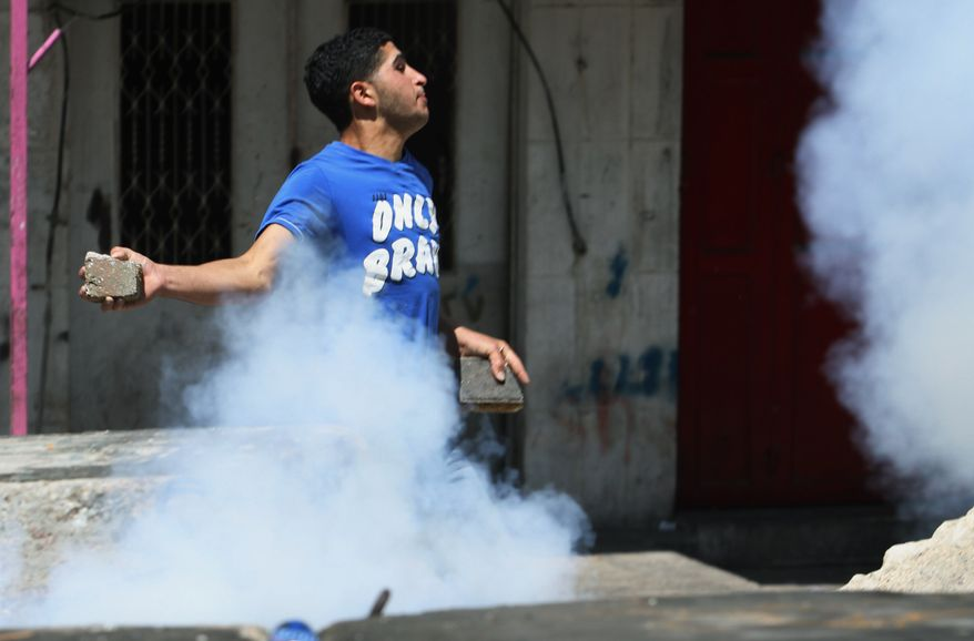 A Palestinian protester throws a piece of concrete at Israeli soldiers during clashes, following a protest against the Israeli military action over Hamas in Gaza, in the West Bank city of Hebron on Friday, Aug. 15, 2014. (AP Photo/Nasser Shiyoukhi) ** FILE **