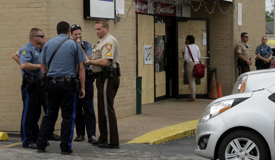Law enforcement officers stand watch outside a market, Friday, Aug. 15, 2014, where Michael Brown allegedly stole some cigars before being killed by police nearly a week ago in Ferguson, Mo. A suburban St. Louis police chief on Friday identified the officer whose fatal shooting ignited days of heated protests, and released documents alleging the teen was killed after a robbery in which he was suspected of stealing a box of cigars. (AP Photo/Charlie Riedel)