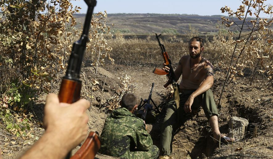 Pro-Russian rebels hold their positions on the frontline near the village of Krasnodon, eastern Ukraine, Friday, Aug. 15, 2014. Russia let Ukrainian officials inspect an aid convoy while it was still on Russian soil Friday and agreed that the Red Cross can distribute the goods in Ukraine's rebel-held city of Luhansk. (AP Photo/Sergei Grits)