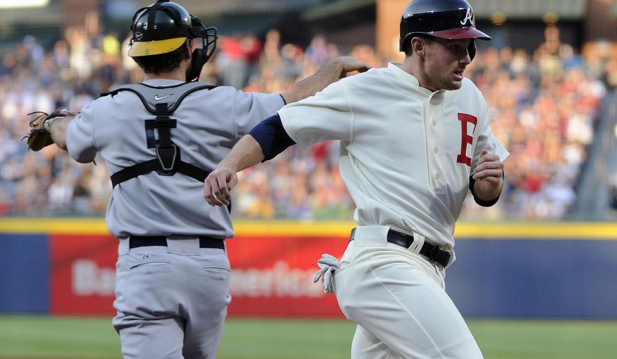 Atlanta Braves' Phil Gosselin, right, scores past Oakland Athletics catcher John Jaso (5) on Freddie Freeman's double during the first inning of a baseball game Saturday, Aug. 16, 2014, in Atlanta. (AP Photo/David Tulis)