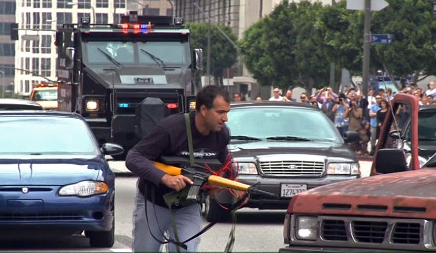 In this July 6, 2013 still frame from a video produced by the Los Angeles Police Department, a man posing as a terrorist runs as a heavily-armored vehicle approaches in a drill simulating a terrorist attack in downtown Los Angeles. After spending a decade sending military equipment to civilian police departments across the United States, Washington is reconsidering the idea in light of the violence in Ferguson, Mo., amid images of heavily-armed police, snipers trained on protesters and tear gas plumes. One night after the violence that accompanied the presence of military-style equipment in Ferguson, the crowd calmed considerably when a police captain walked through the crowd, unprotected, in a gesture of reconciliation. The contrast added to the perception that the tanks and tear gas had done more harm than good. (AP Photo/Los Angeles Police Department)