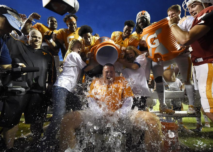 Tennessee coach Butch Jones, center, gets a cooler of ice dumped on him while participating in the Ice Bucket Challenge at the conclusion of the Tennessee football team's open practice at Neyland Stadium in Knoxville, Tenn., on Saturday, Aug. 16, 2014. (AP Photo/Knoxville News Sentinel, Adam Lau)