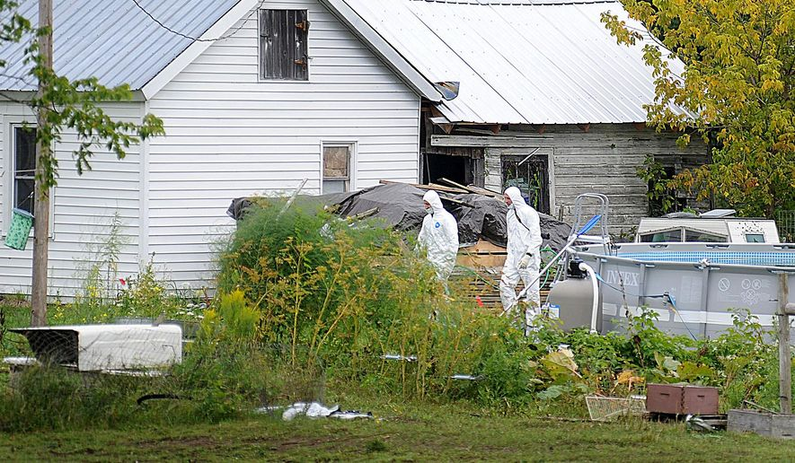 A pair of investigators walk on the property of Stephen Howells II and Nicole F. Vaisey, in Hermon, N.Y., Saturday, Aug. 16, 2014. Vaisey and Howells were arrested Friday on charges of first-degree kidnapping with the intent to physically harm or sexually abuse the victims. (AP Photo/Watertown Daily Times, Melanie Kimber Lago) MANDATORY CREDIT, SYRACUSE OUT