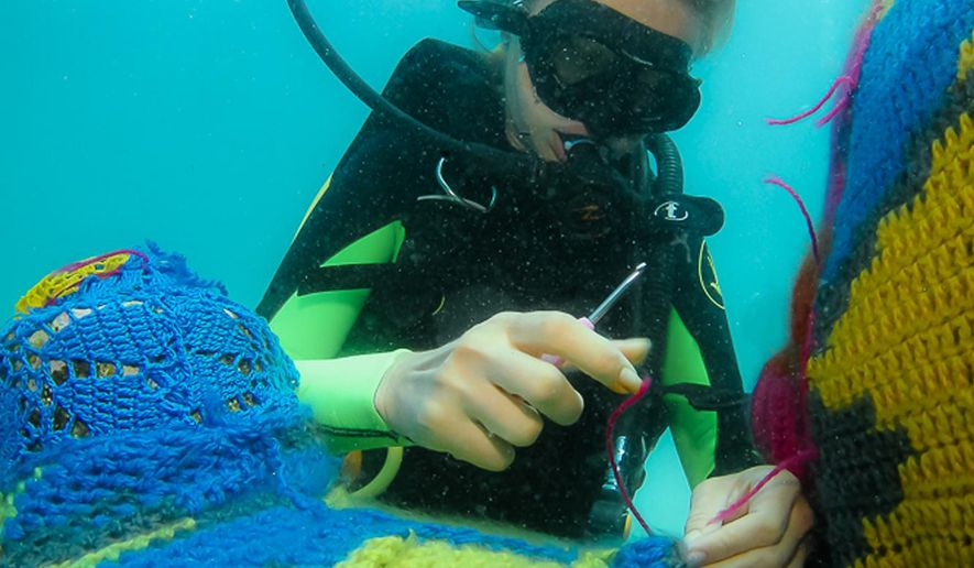 In this undated photo, provided by the Polish artist Agata Oleksiak, shows her setting up her installation over an underwater sculpture at the Cancun Underwater Museum near Cancun, Mexico. The artist known as Olek, famed for slipping crocheted covers around unlikely objects has run afoul of environmental authorities in Mexico for slipping her brightly colored work around the underwater sculptures. (AP Photo)