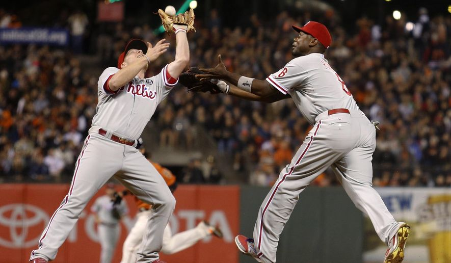 Philadelphia Phillies first baseman Ryan Howard, right, watches as third baseman Cody Asche catches an infield fly ball hit by San Francisco Giants' Madison Bumgardner to end the sixth inning of a baseball game, Friday August 15, 2014, in San Francisco. (AP Photo/Beck Diefenbach)