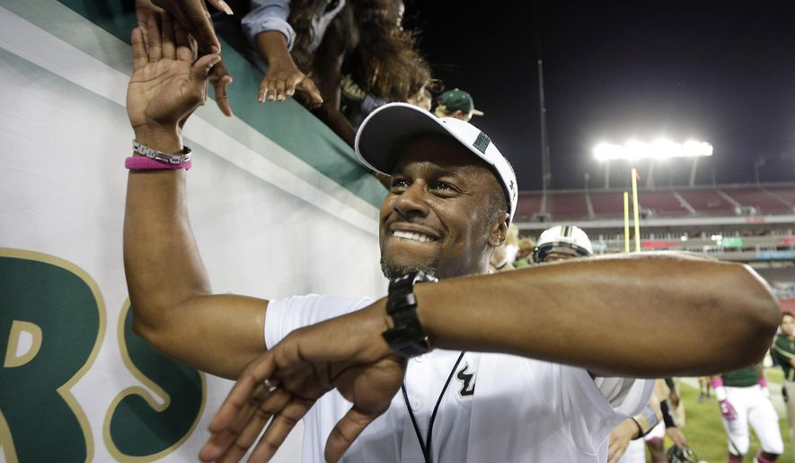 FILE - In this Oct. 5, 2013, file photo, South Florida head coach Willie Taggart celebrates with fans after the team defeated Cincinnati during an NCAA college football game in Tampa, Fla. Now that Chris Petersen has left Boise State for Washington, college football needs another coach from outside the so-called Big 5 conferences that will have his name come up for almost every big job. (AP Photo/Chris O'Meara, File)