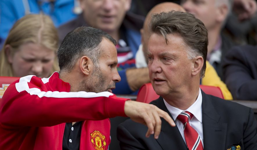 Manchester United's manager Louis van Gaal, right, takes his seat alongside assistant coach Ryan Giggs before the team's English Premier League soccer match against Swansea City at Old Trafford Stadium, Manchester, England, Saturday Aug. 16, 2014. (AP Photo/Jon Super)