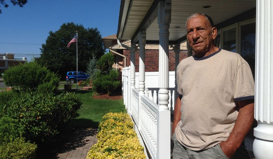 In this Aug. 13, 2014 photo, Jerry Baggetta poses for a photo outside his home in Commack, N.Y., on New York's Long Island. Baggetta is among a group of Commack residents opposing a proposal to bring as many as 40 unaccompanied immigrant children to be housed at the nearby Holy Cross Lutheran Church. (AP Photo/Frank Eltman)