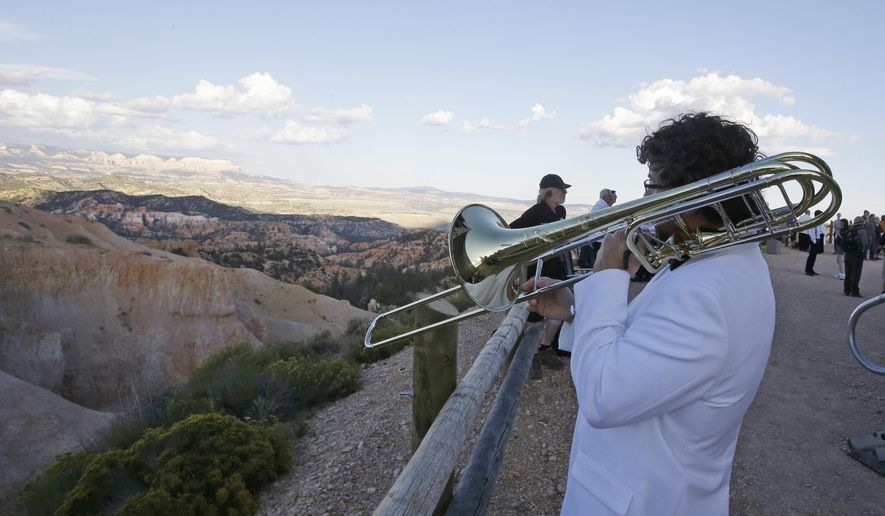 Graeme Mutchler warms up with his trombone during rehearsal before the Utah Symphony performance Friday, Aug. 15, 2014, at the edge Bryce Canyon National Park, Utah. The Utah Symphony hopes to complement the beauty of Utah's soaring red rocks and canyons with free desert performances near Utah's national parks this weekend. The 75-piece orchestra is set to perform Friday near Bryce Canyon and Saturday near Zion National Parks. (AP PHoto/Rick Bowmer)