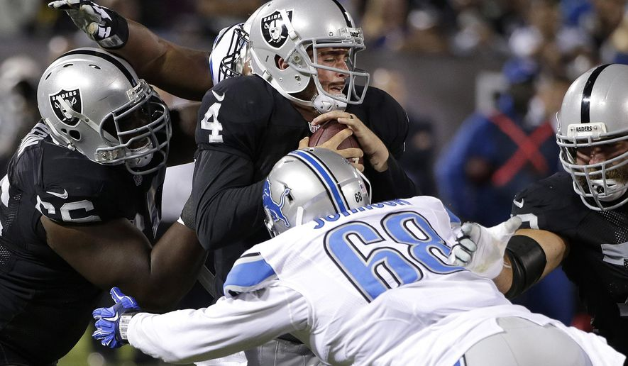 Oakland Raiders quarterback Derek Carr (4) is tackled by Detroit Lions defensive end George Johnson (68) and defensive tackle Andre Fluellen, rear, during the third quarter of an NFL preseason football game in Oakland, Calif., Friday, Aug. 15, 2014. (AP Photo/Marcio Jose Sanchez)