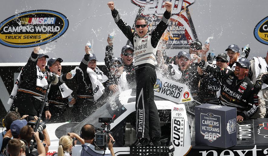 Driver Johnny Sauter, center, celebrates in Victory Lane after winning the NASCAR Camping World truck series auto race at Michigan International Speedway in Brooklyn, Mich., Saturday, Aug. 16, 2014. (AP Photo/Paul Sancya)