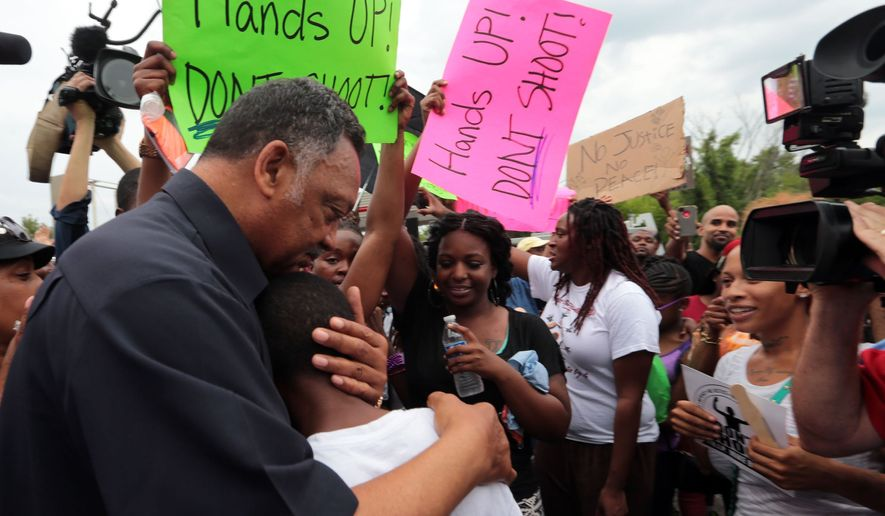 ** FILE ** Civil rights leader Rev. Jesse Jackson hugs Jakailin Johnson, 11, as he greets a group of protestors on Friday, Aug. 15, 2014, who gathered to demonstrate for justice in the Michael Brown shooting at the burned QuikTrip in Ferguson. (AP Photo/St. Louis Post-Dispatch, Laurie Skrivan)