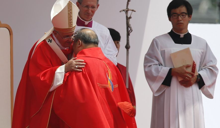 Pope Francis, left, hugs with South Korean cardinal Andrew Yeom Soo-Jung during the holy mass in front of Gwanghwamun Gate in Seoul on Saturday. Pope Francis beatified 124 Korean martyrs on Saturday. (AP Photo/Issei Kato, Pool)
