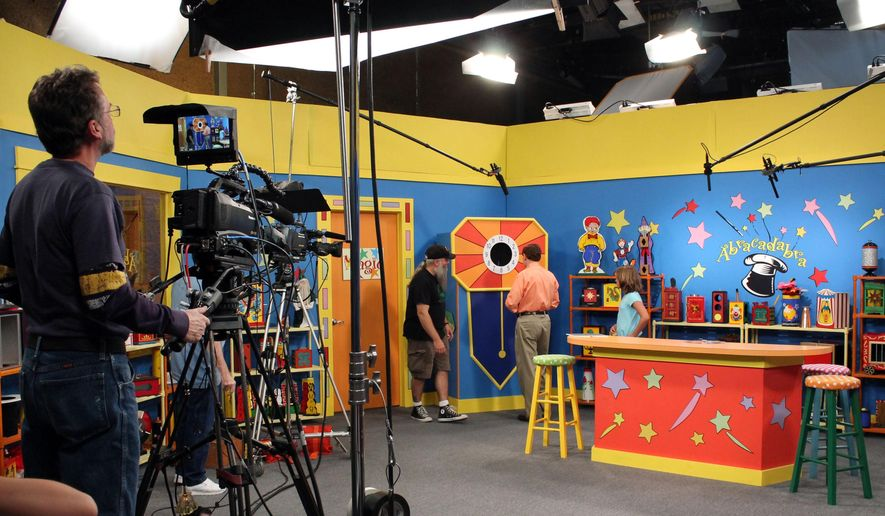 """In this photo taken on Aug. 4, 2014, from rear left, director Larry Dowling, host Dr. Mike Adelman and actress Grace Goggins map out a scene while filming an episode of """"Abracadabra"""" about bullying in Charlston, W.Va. The West Virginia Public Broadcasting educational show is designed for children ages 4-10. (AP Photo/The Charleston Gazette, Anna Patrick)"""