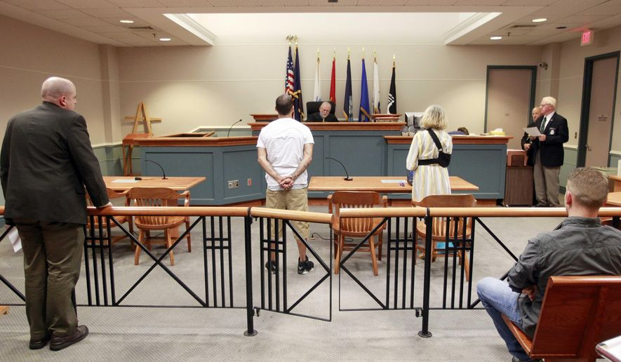 In this photo taken Thursday, Aug. 7, 2014, in Nashua, N.H. Judge James Leary presides over a case with war veteran William Santana, second from left. It is New Hampshire's first court dedicated to veterans facing criminal charges.  (AP Photo/Jim Cole)