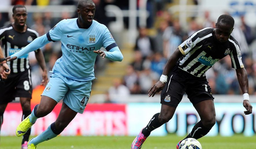 Newcastle United's Moussa Sissoko, right, vies for the ball with Manchester City's Yaya Toure, left, during their English Premier League soccer match at St James' Park, Newcastle, England, Sunday, Aug. 17, 2014. (AP Photo/Scott Heppell)