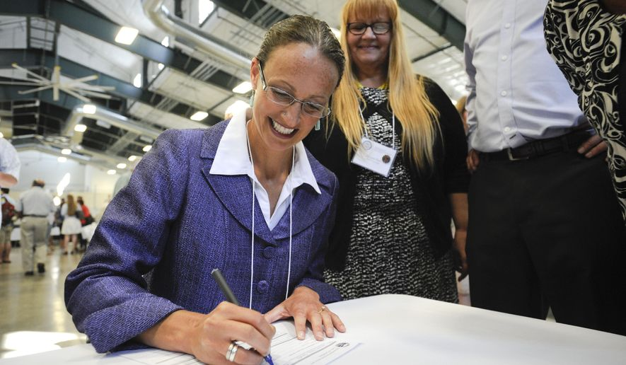 Amanda Curtis, a state legislator from Butte, Mont. fills out paperwork after she was selected as the replacement candidate for the U.S. Senate race against Republican Rep. Steve Daines, in Helena, Mont. on Saturday, Aug. 16, 2014. (AP Photo/Independent Record, Thom Bridge)