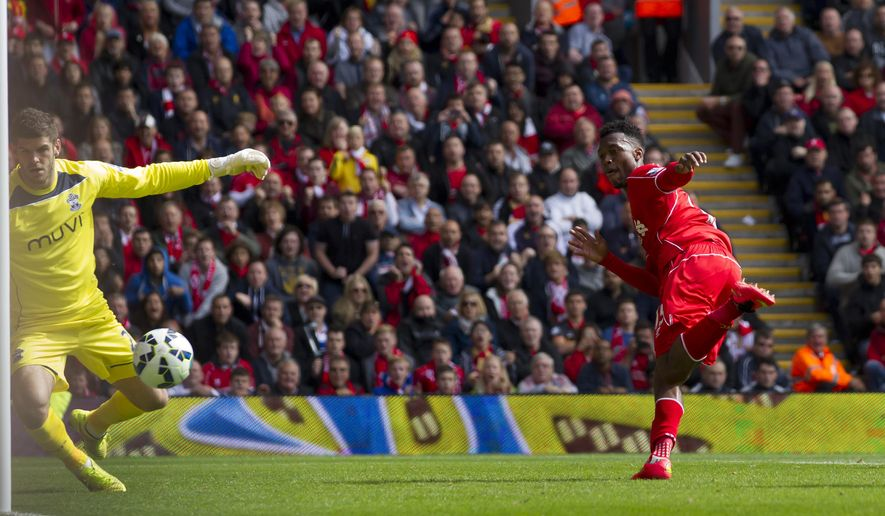 Liverpool's Daniel Sturridge, right, scores past Southampton's Fraser Forster during their English Premier League soccer match at Anfield Stadium, Liverpool, England, Sunday Aug. 17, 2014. (AP Photo/Jon Super)