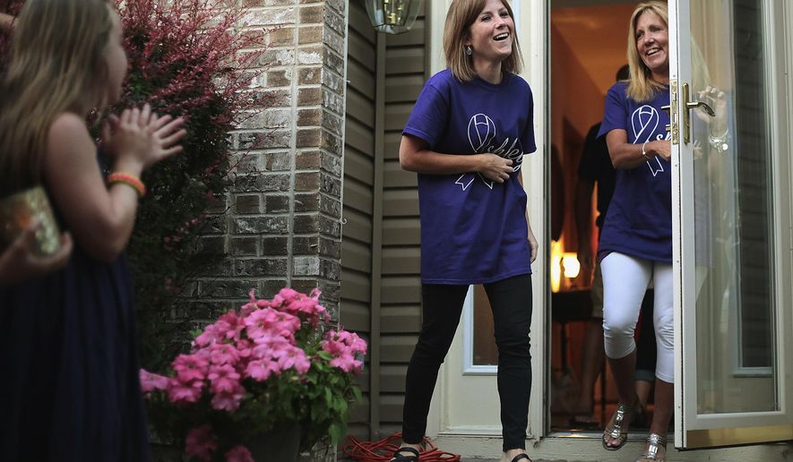 In this July 30 2014 photo, Ashley Kelley, who suffers from epilepsy, walks out her front door with her mother, Gail, to a surprise vigil outside of her home in Crystal Lake, Ill. Ashley will be the first at Rush University Medical Center to receive a NeuroPace implant now that it's been FDA approved after a 10-year trial. The hope is that the NeuroPace controls or reduces or maybe even completely stops all the seizures Kelley suffers. She has between 15 and 20 of them a month. (AP Photo/Northwest Herald, Kyle Grillot)  MANDATORY CREDIT