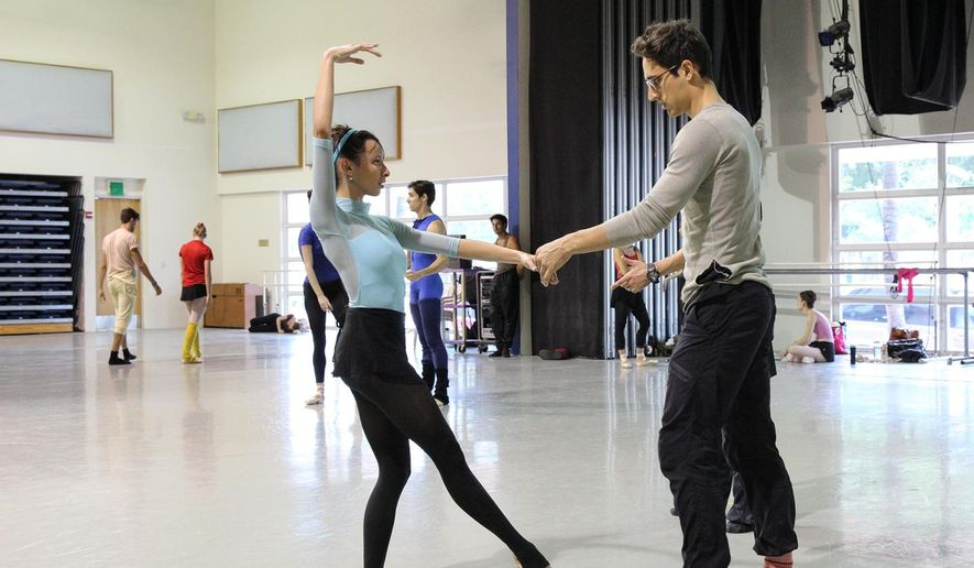In this July 31, 2014 photo provided by the Miami City Ballet, choreographer Justin Peck, right, works with a dancer in the studio in Miami Beach, Fla. Miami City Ballet will debut in March a new work that is a collaboration between Peck and street artist Shepard Fairey. Peck is a soloist and choreographer at New York Ballet. (AP Photo/Miami City Ballet, Daniel Azoulay)