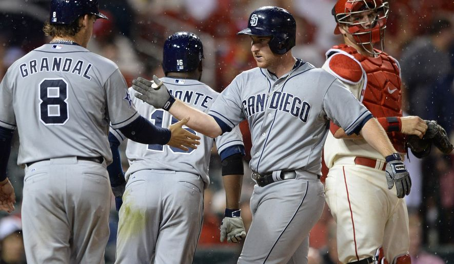 San Diego Padres' Jedd Gyorko, second from right, is congratulated by teammates Yasmani Grandal (8) and Abraham Almonte (16) after his grand slam as St. Louis Cardinals' A.J. Pierzynski, right, looks away in the seventh inning in a baseball game, Saturday, Aug. 16, 2014, at Busch Stadium in St. Louis. (AP Photo/Bill Boyce)