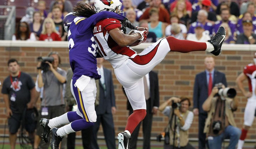 Arizona Cardinals wide receiver Larry Fitzgerald, right, catches a pass in front of Minnesota Vikings cornerback Marcus Sherels, left, during the first half of an NFL preseason football game, Saturday, Aug. 16, 2014, in Minneapolis. (AP Photo/Ann Heisenfelt)