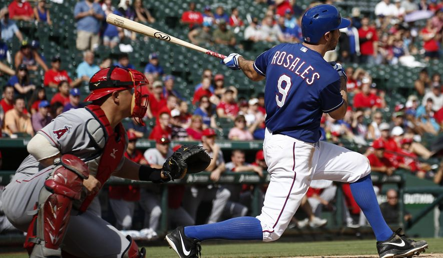 Texas Rangers' Adam Rosales (9) follows through on his game winning single in front of Los Angeles Angels catcher Hank Conger (24) during the ninth inning of a baseball game, Sunday, Aug. 17, 2014, in Arlington, Texas. The Rangers won 3-2. (AP Photo/Jim Cowsert)