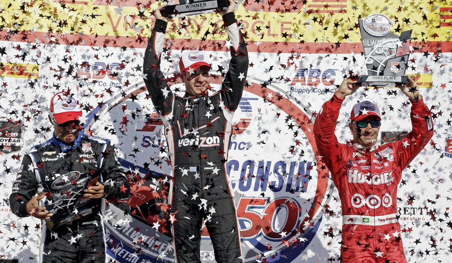 Winner Will Power is flanked by second place finisher Juan Pablo Montoya, left, and third place finisher Tony Kanaan after the Milwaukee Mile IndyCar auto race Sunday, Aug. 17, 2014, in West Allis, Wis. (AP Photo/Morry Gash)