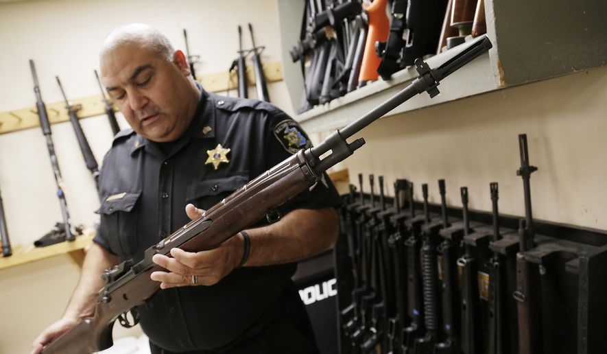 Macomb County Sheriff Sgt. Phil Abdoo shows an M14 rifle acquired through a federal government program at the range at the Macomb County Sheriff's department in Mt. Clemens, Mich., Thursday, July 17, 2014. (AP Photo/Detroit Free Press, Mandi Wright)